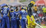 A dejected Chris Gayle (right) walks off as the Barbados Tridents celebrate