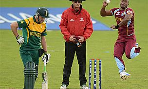 Tino Best bowls for West Indies as AB de Villiers looks on