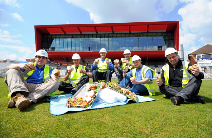 The construction workers from Morgan Ashurst being treated to a picnic on the Old Trafford Cricket pitch.